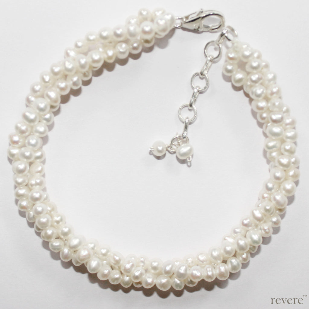 71238f568 Royale features 3 strings of exquisite white oval freshwater pearls twisted  together and fastened by a