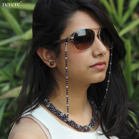 "The Sashay eyewear chain is handmade in dark grey freshwater pearls dispersed with glass crystal. This piece has sterling silver lobster clasps at both ends, for easy clipping on. Also shown here is the ""Sashay"" necklace."