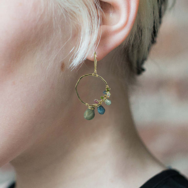 Gold hoop earring with asymmetrical gemstone wraps