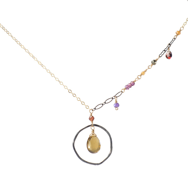 Gold pendant necklace with asymmetrical gemstone drops and multiple chain styles