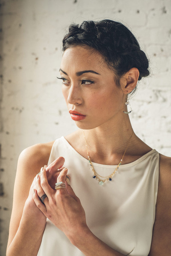 Model wearing the bejeweled triple tier necklace in gold metal and oceanic collection gemstones