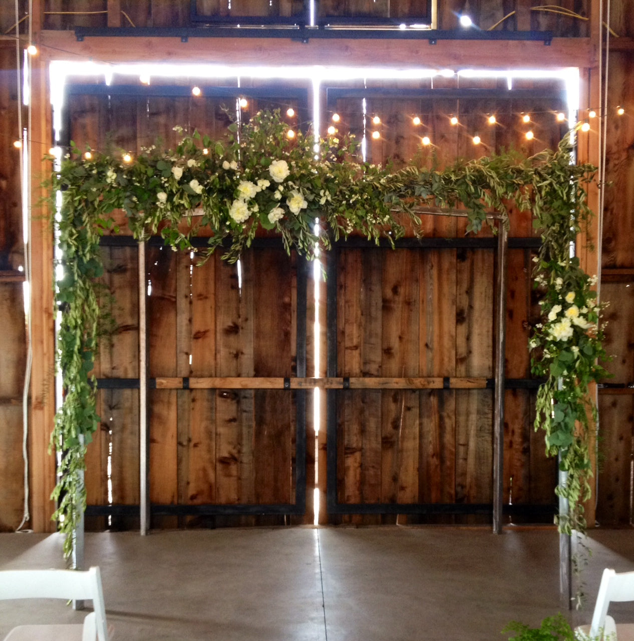 Large foliage and floral arch for a wedding in a barn by Gorgeous and Green