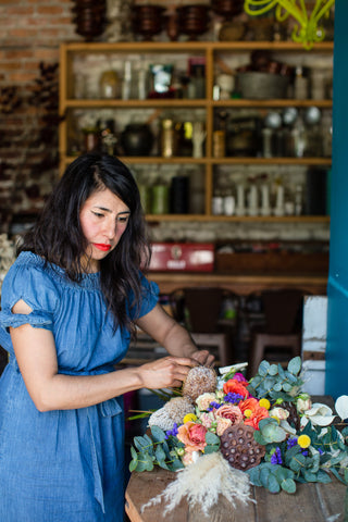 Pilar Zuniga of Gorgeous and Green adding in blooms and textures to a floral door swag