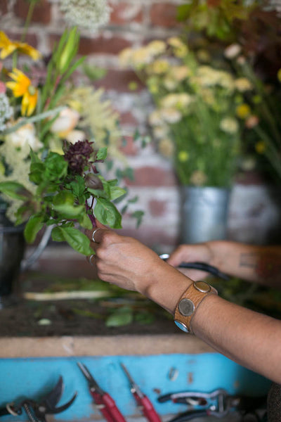 Pilar Zuniga's hands working on a local floral design, without floral foam