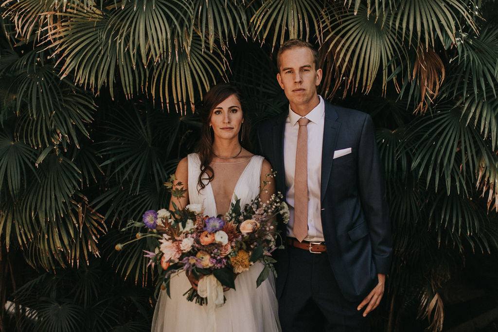 Bride and Groom under palm fronds with Gorgeous and Green wedding florals