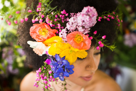 Closeup of some flowers in a model's hair during a bathtub floral photo shoot at Pilar Zuniga's home in Oakland