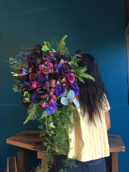 Oversized bridal bouquet in purples, blue and violets  over my shoulder by Gorgeous and Green