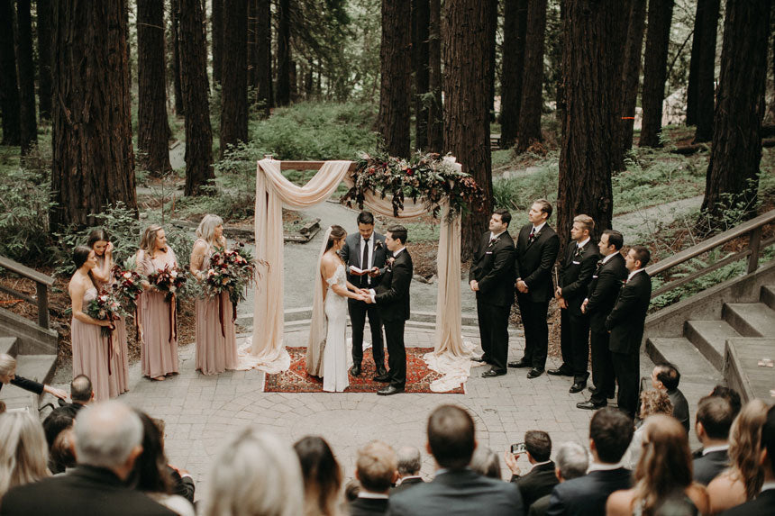 The Beautiful and simple archway created by the couple, adorned with a burst of burgundy blooms and foliage by G&G. Photo by From the Daisies.