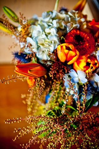 Closeup of the orange and blue color scheme wedding reception flowers by gorgeous and green