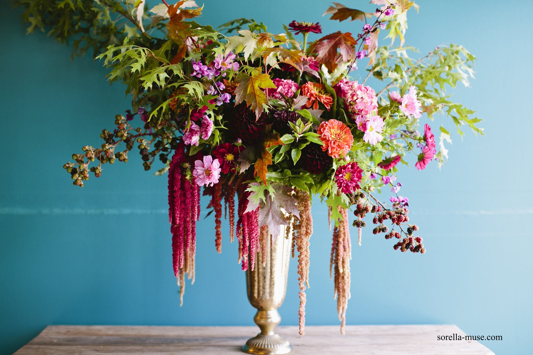 teal wall with burgundy and pink draping florals in a pedestal vase