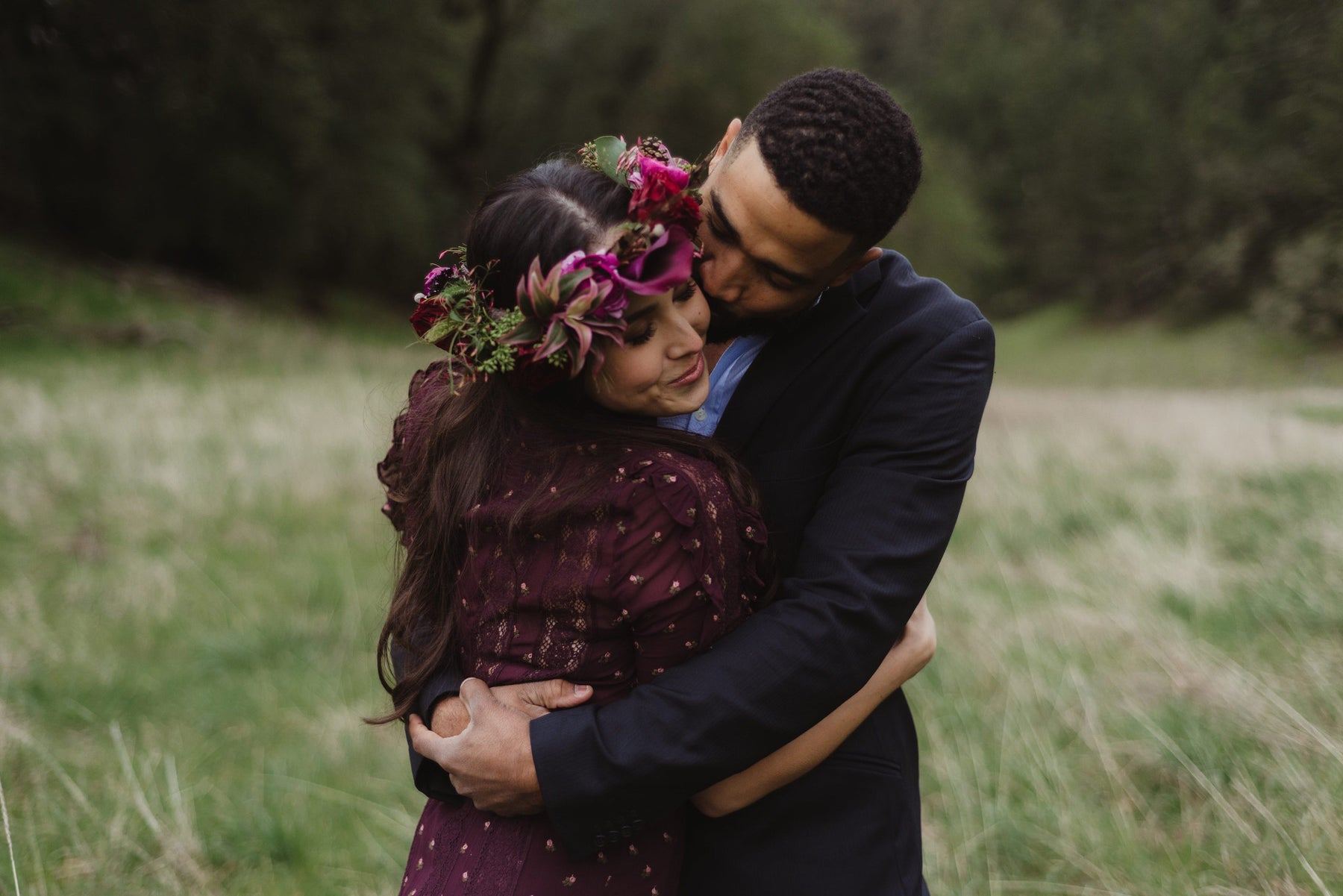 A couple entwined in an embrace, with a flower garland hair piece