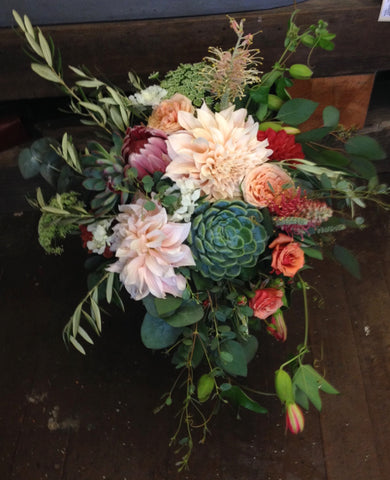 Beautiful bridal bouquet in coral and peach by Gorgeous and Green featuring local grown dahlias, succulents, garden roses, passion vine, olive, protea and other textures.