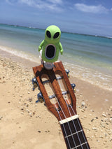 Green alien tuner on ukulele at beach hawaii