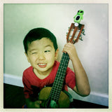 boy playing ukulele green alien tuner