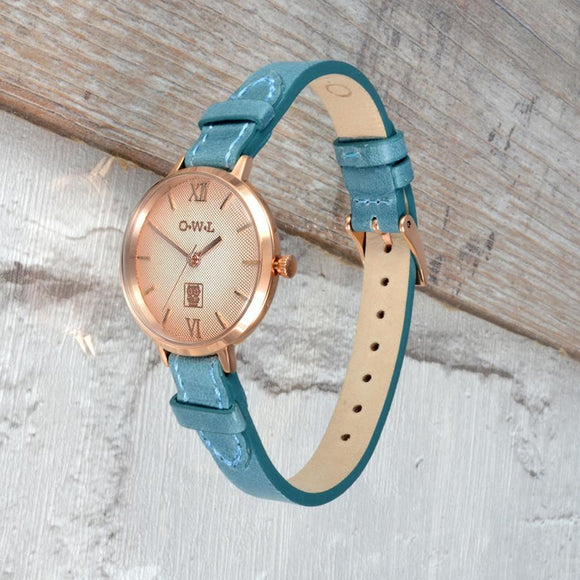 Rose gold ladies leather watch with a soft graduated dial and teal blue strap