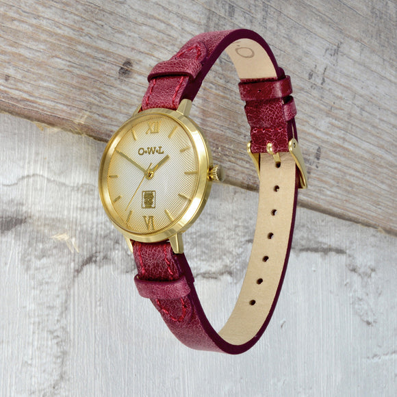 Gold vintage styled ladies watch with a leather strap and textured dial
