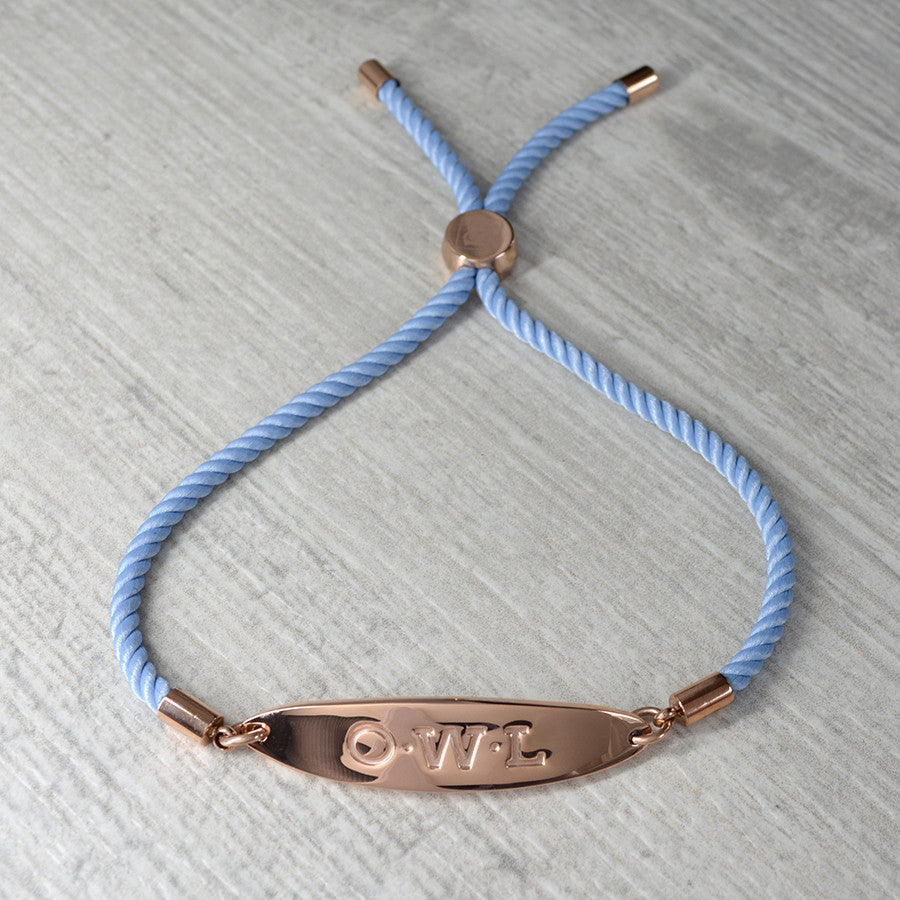 Metal friendship bracelet in rose gold with a pale blue cord