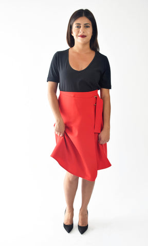 Image of a brunette model wearing a black, n-neck t-shirt with a red skirt and black heals.
