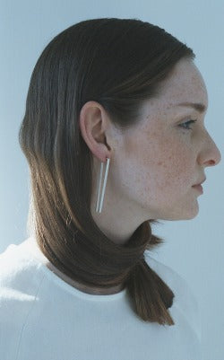 Colour image of a profile shot of a red-headed model with her hair wrapped around her neck, wearing silver earrings