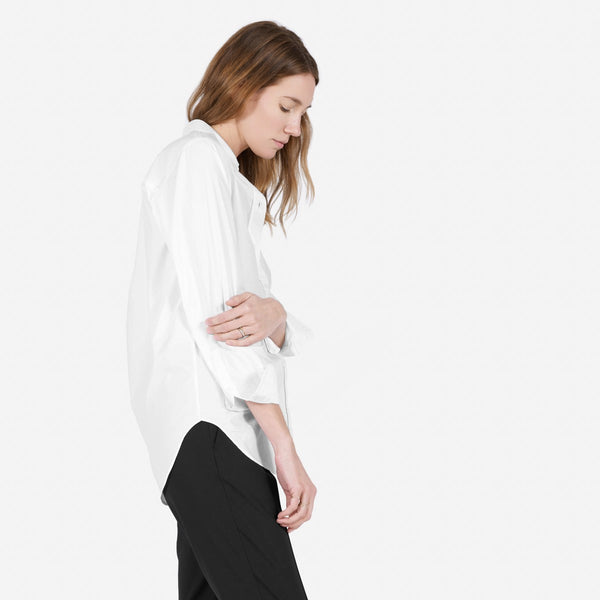 Blonde model wearing an Everlane white dress shirt.