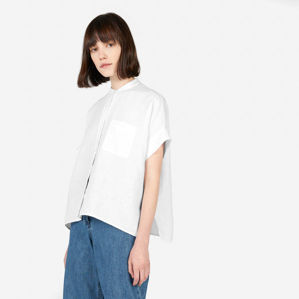 Photo of a brunette model wearing a white linen top by Everlane in front of a white background.