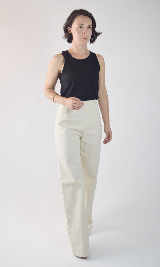 Photo of a brunette woman with chin-length hair wearing white, high-waisted, wide-legged pants with a black tank top, standing in front of a white backdrop.
