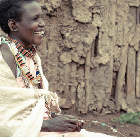 maasai woman making bush bead necklace