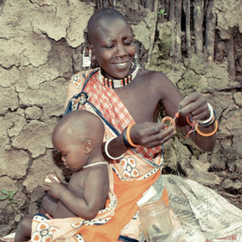 maasai mom and child making bush bead jewelry