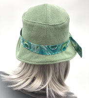 Eleanor cloche hat in fern green wool with Peacock hat band rear view