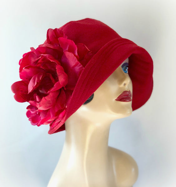 Hat model wearing a red wool cloche with a large red flower side view