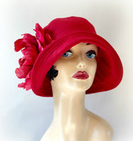 Hat model wearing a red wool cloche with a large red flower front view