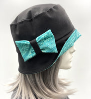 showerproof bucket hat in black with turquoise contrast side bow view