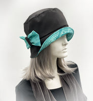 showerproof bucket hat in black with turquoise contrast