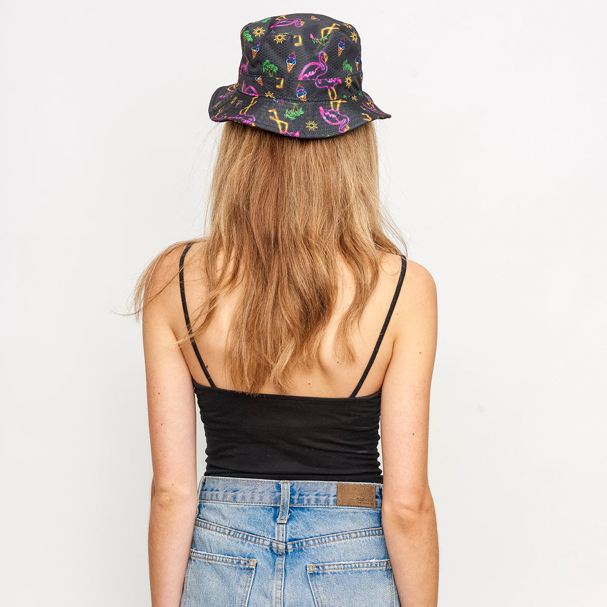 back view of female wearing black rave bucket hat with neon flamingos