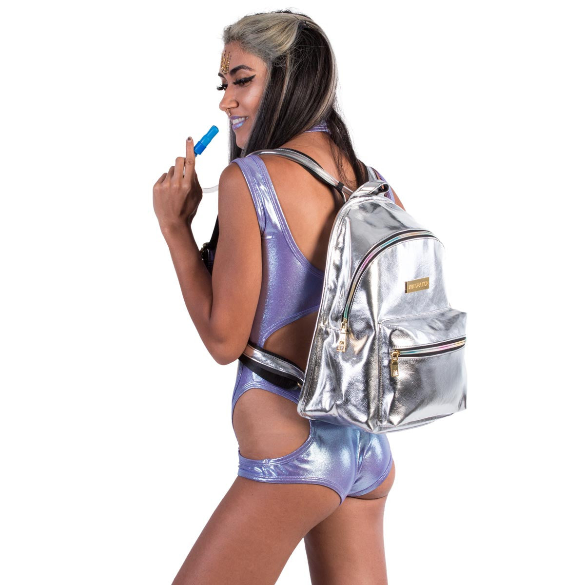 Female wearing platinum silver leather hydration pack with rainbow zippers.