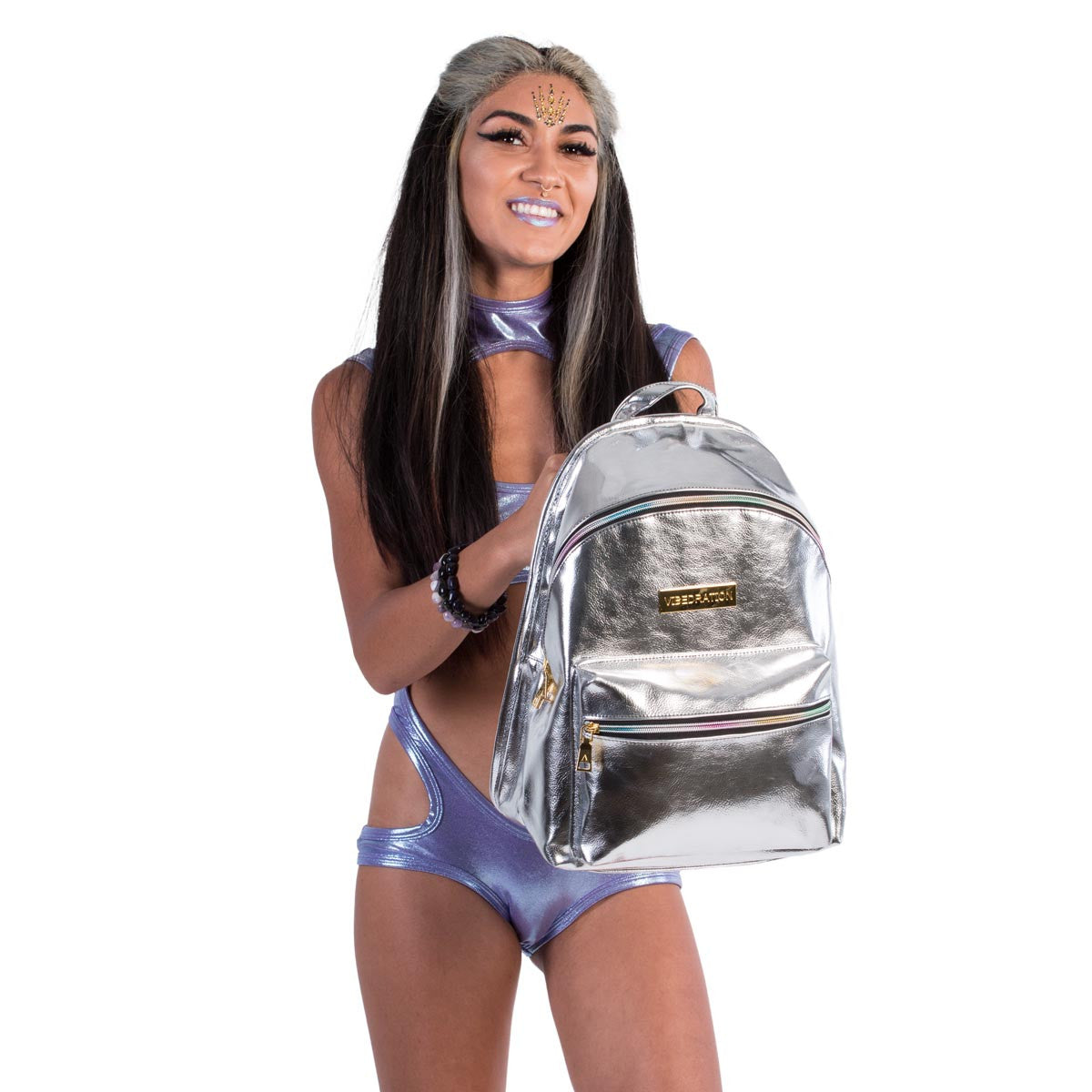 Female holding platinum silver leather hydration pack with rainbow zippers.
