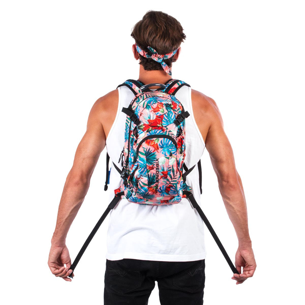 Back view of male wearing coral Hawaiian water backpack.