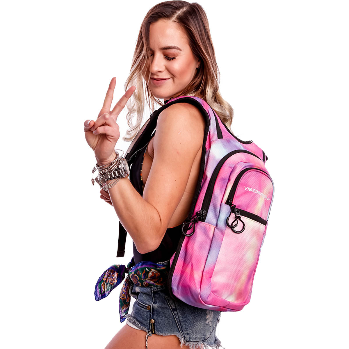 Female wearing tie-dye pink hydration pack with three pockets.