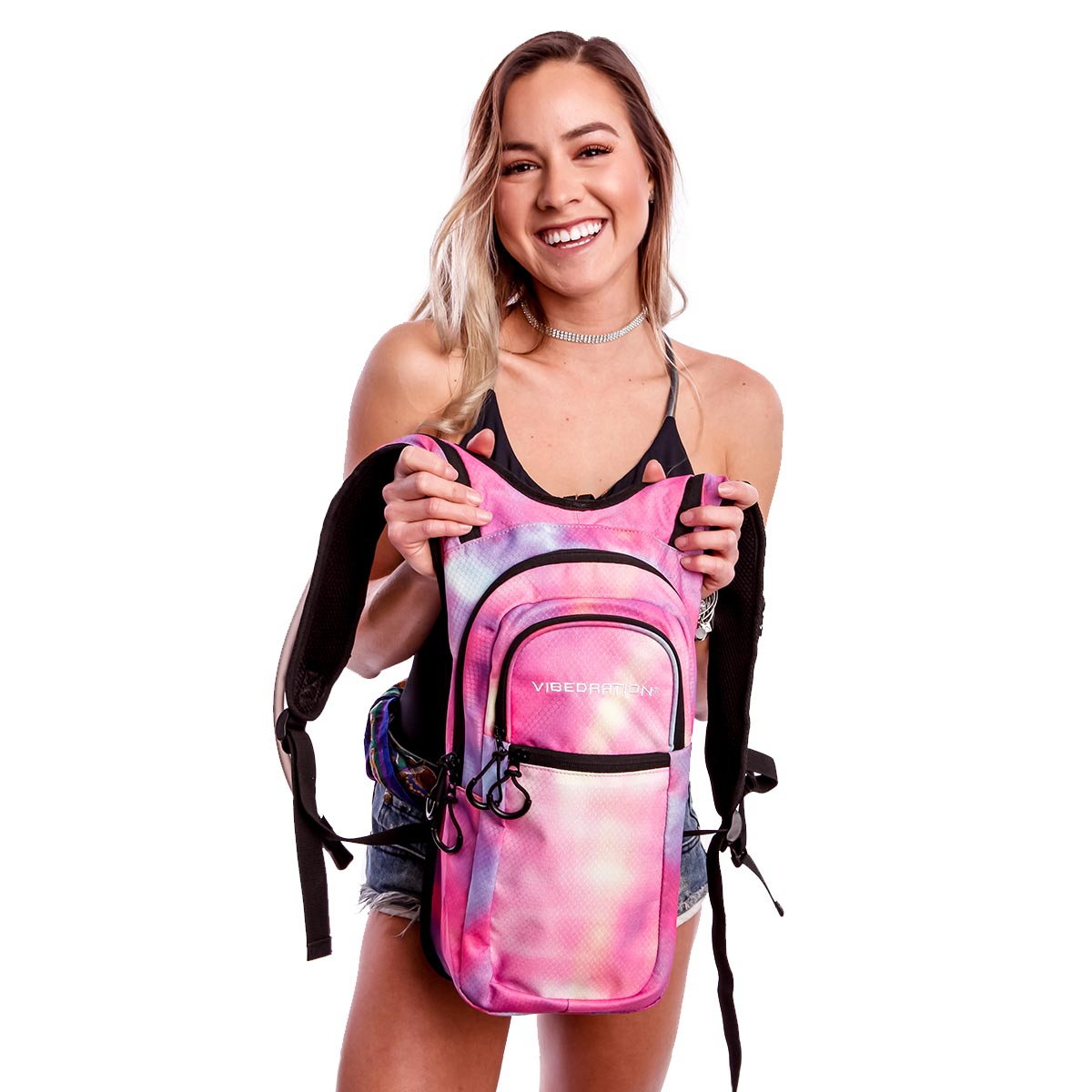 Female holding Tie-Dye Pink hydration pack with three pockets.