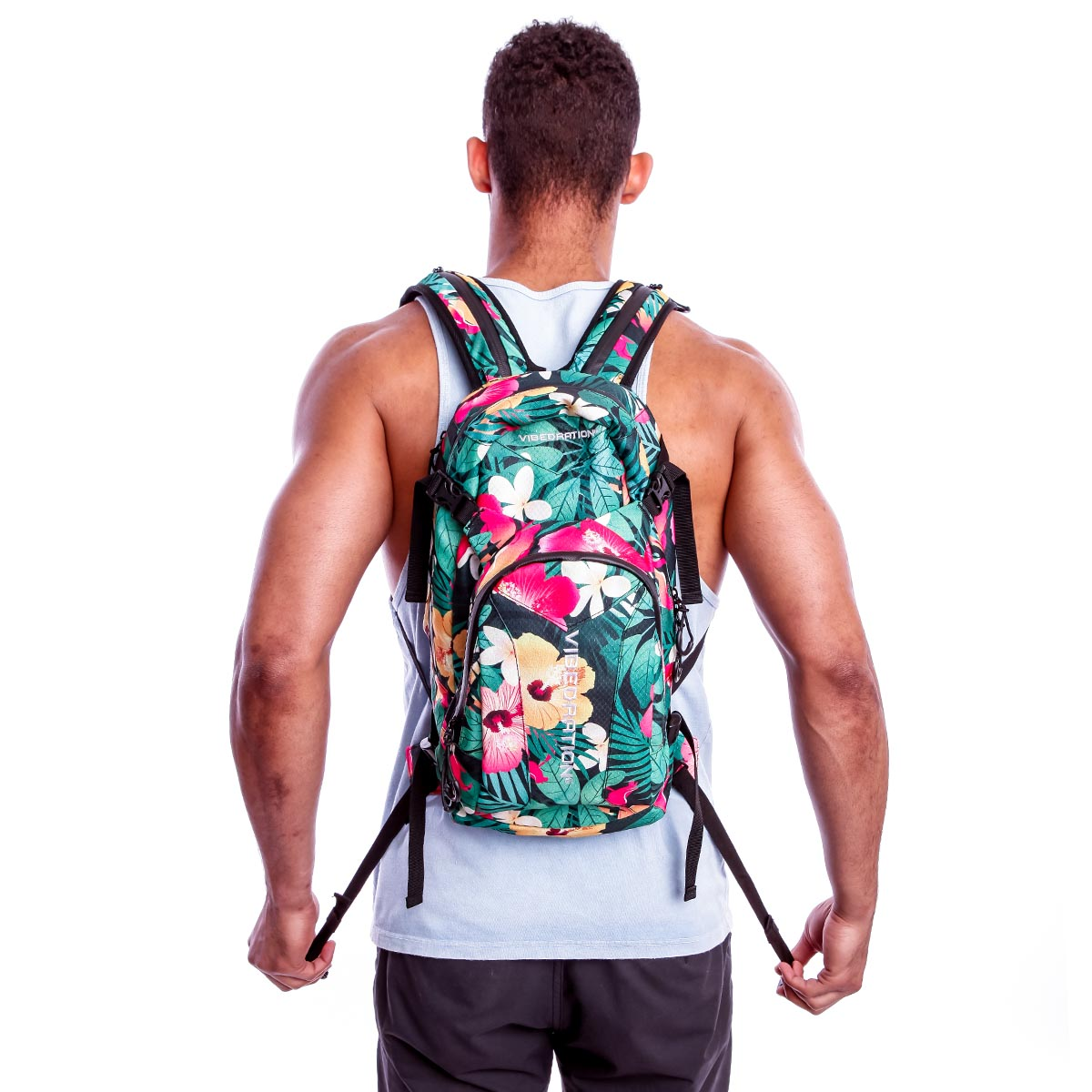 Back view of male wearing green hawaiian print camping backpack with 3 Liter water capacity.
