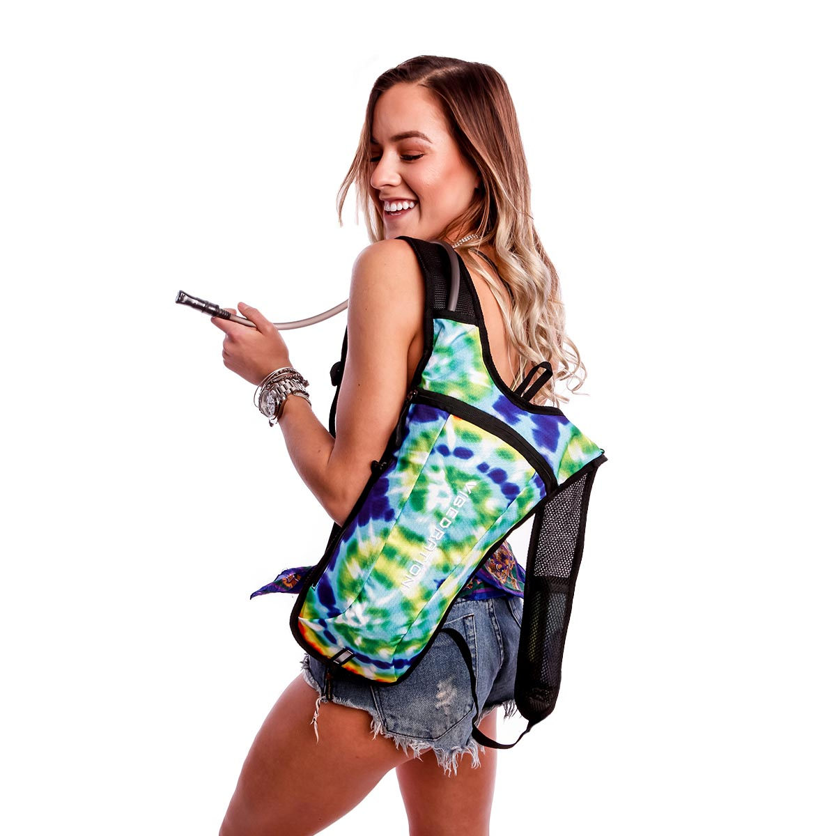 a girl with jean shorts wearing the tie-dye classic hydration pack