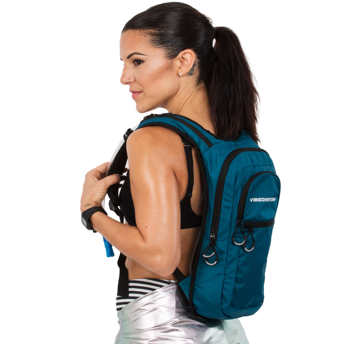 Side view of female wearing dark blue nylon hydration pack with three compartments.