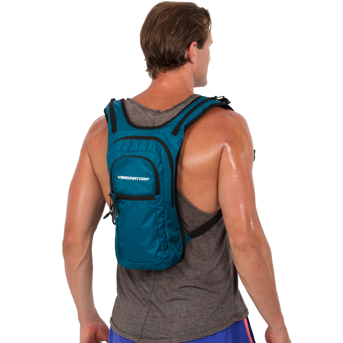 Side view of male wearing dark blue nylon hydration pack with three compartments.