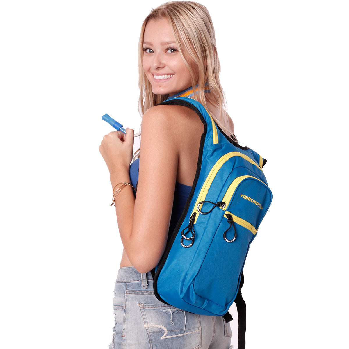 Female wearing baby blue and yellow hydration pack with three pockets.