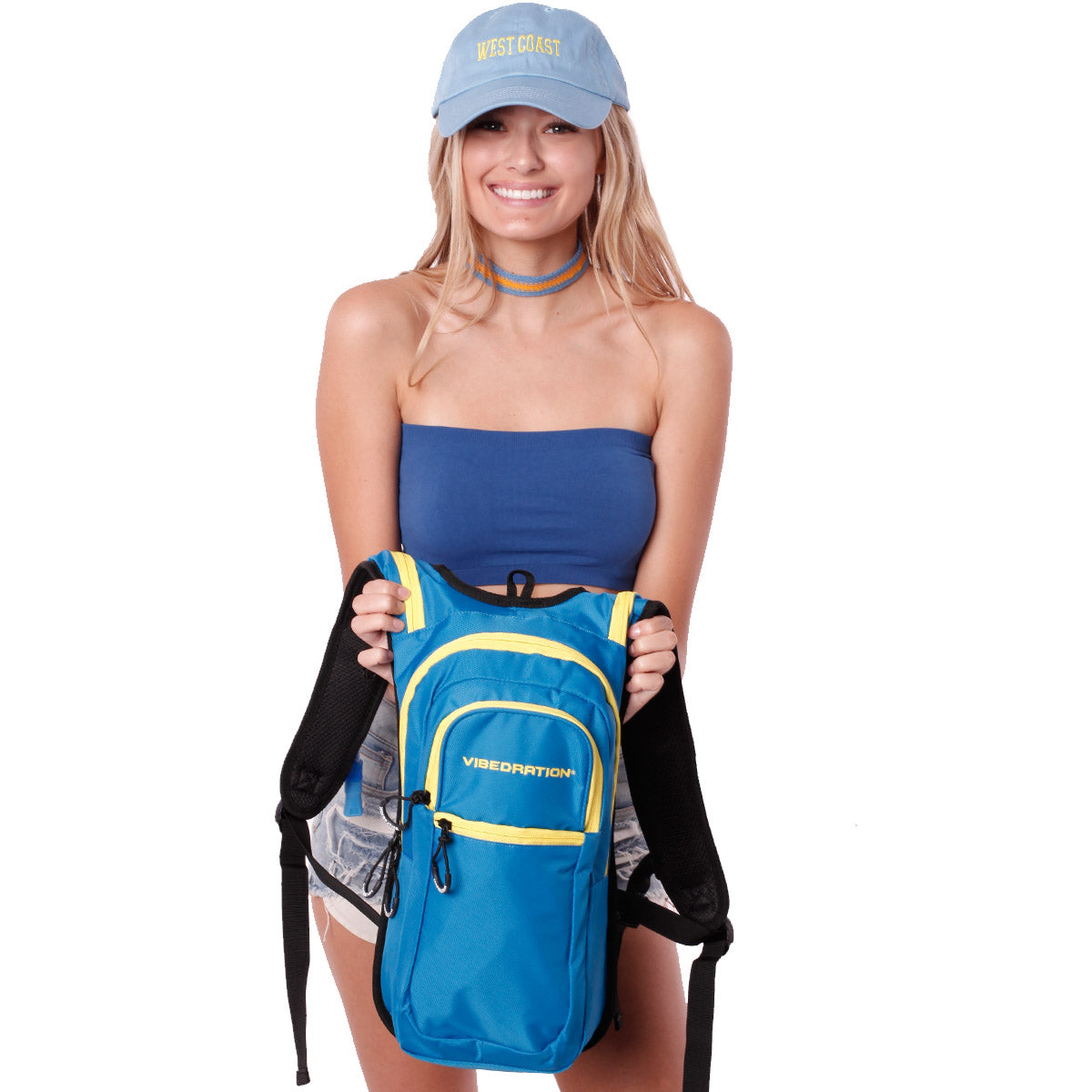 Female holding baby blue and yellow hydration pack with three pockets.