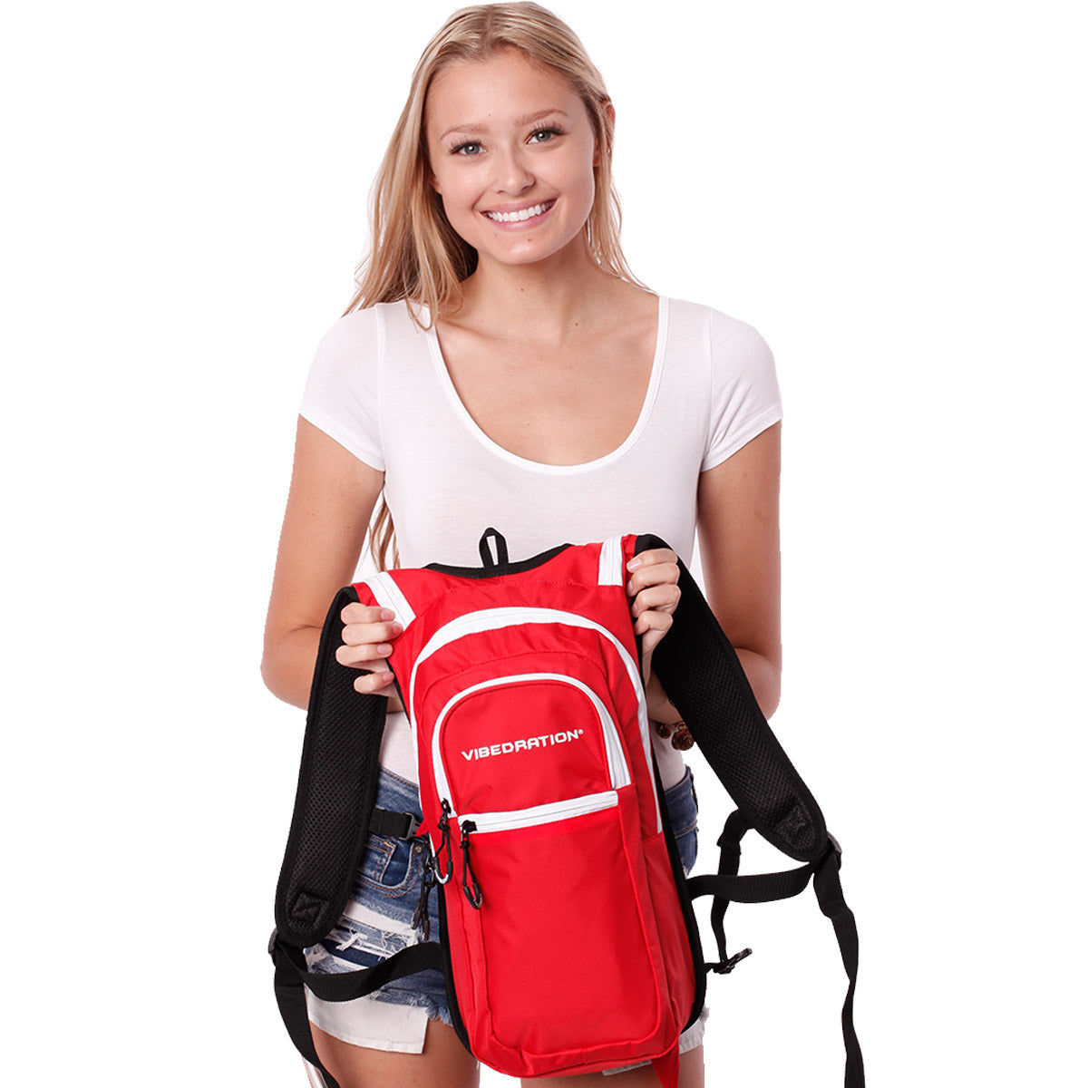 Female holding red and white hydration pack with three pockets.
