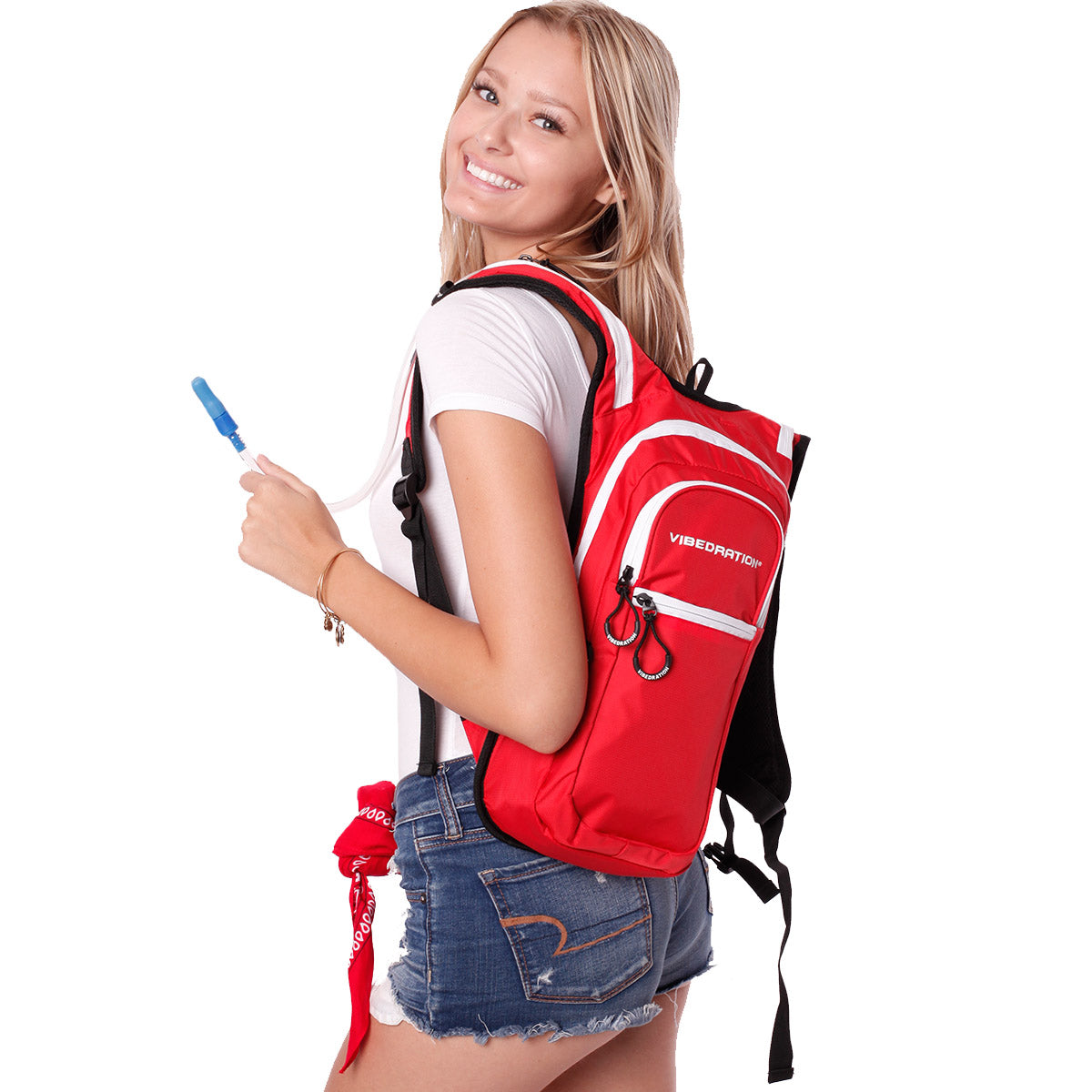 Side view of female wearing red and white hydration pack with three pockets.