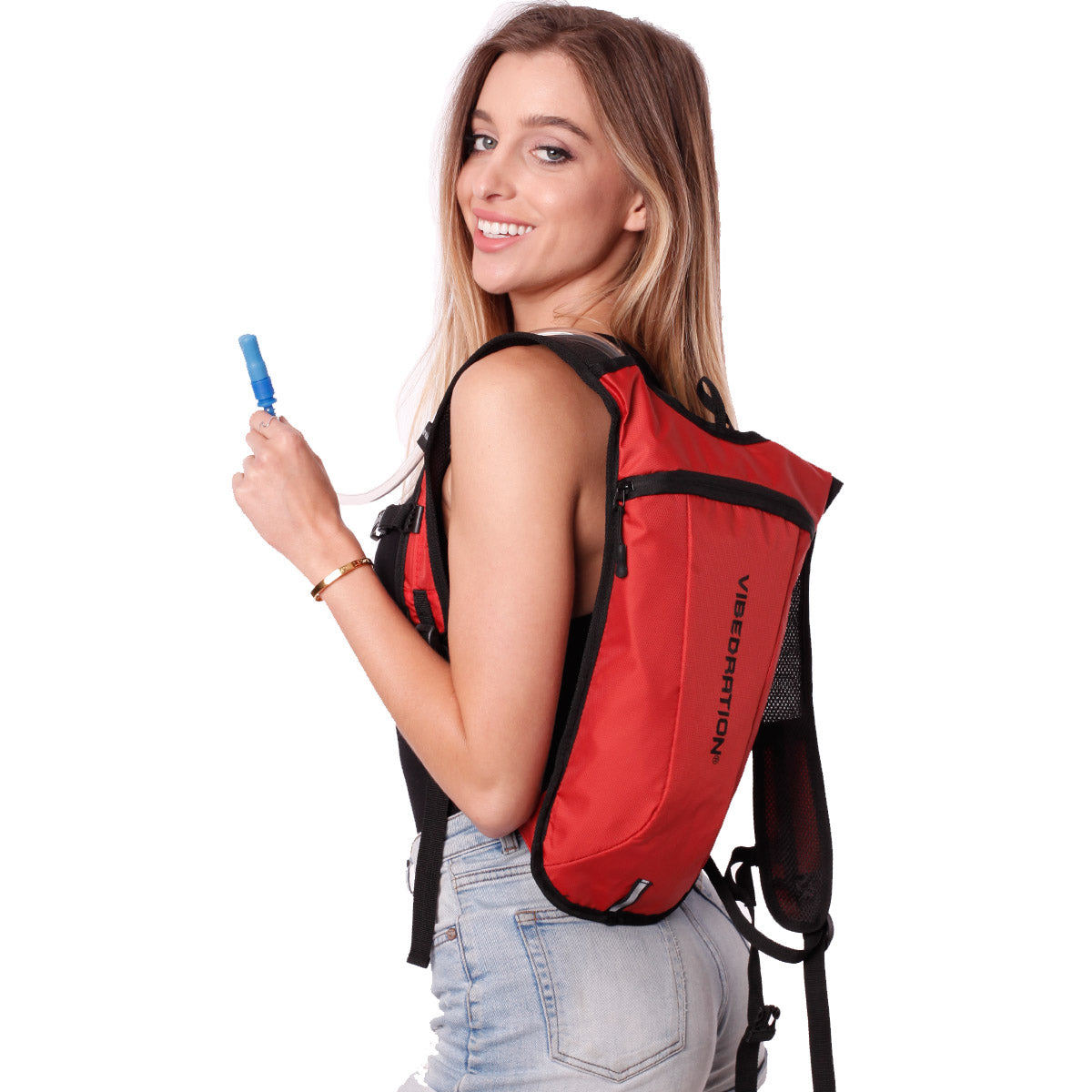 Side view of female wearing dark orange hydration backpack.