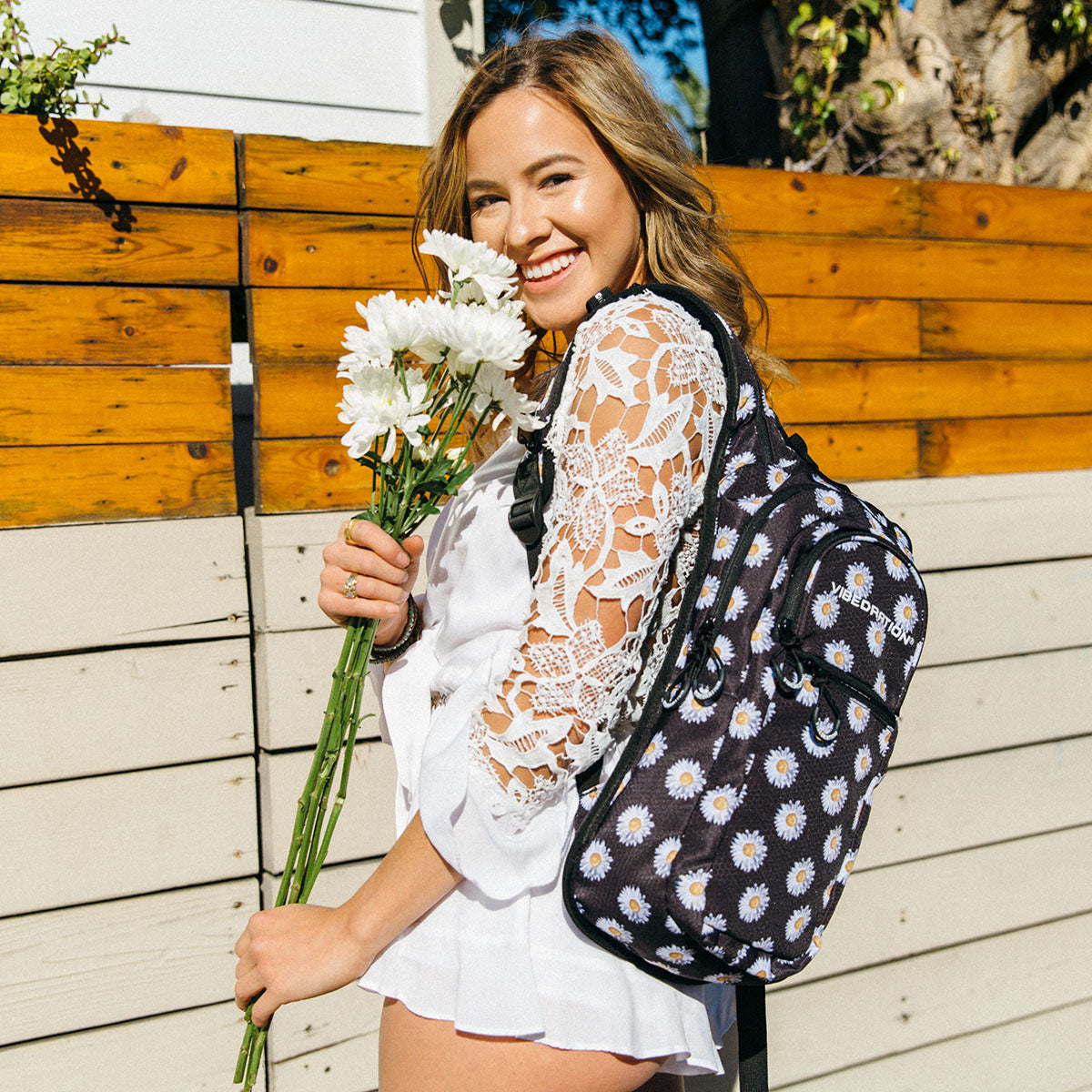 Female wearing black daisy water backpack