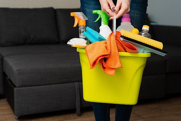 1. cleaning products being carried in a yellow bucket